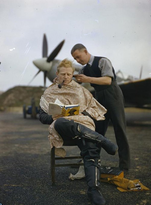 Pilot wearing aviator combat boots while he smokes a pipe and gets his hair cut