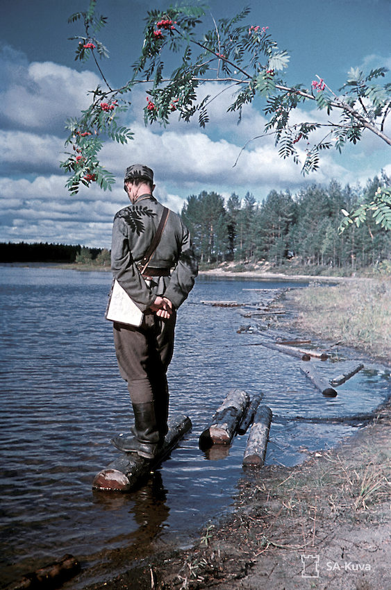 Finnish soldier Olavi Paavolainen stands on a log in a lake.