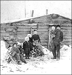 Minnesota family in front of log cabin, 1890.
