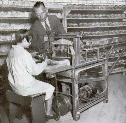 A bread slicer in use, 1930.