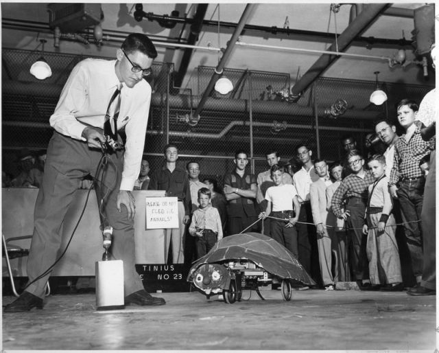 An engineering student takes a robot through its paces, 1950.