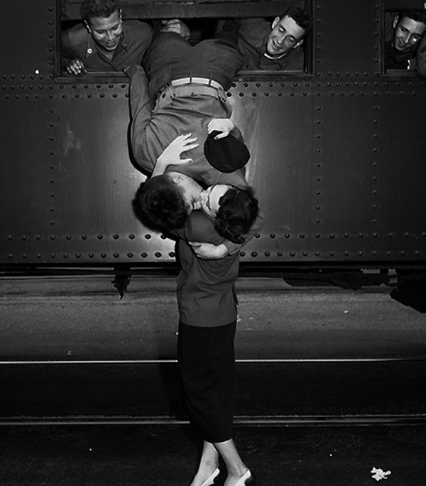 a soldier leaning out of a train to kiss his girl goodbye.