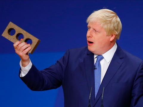 Boris Johnson holding a brick