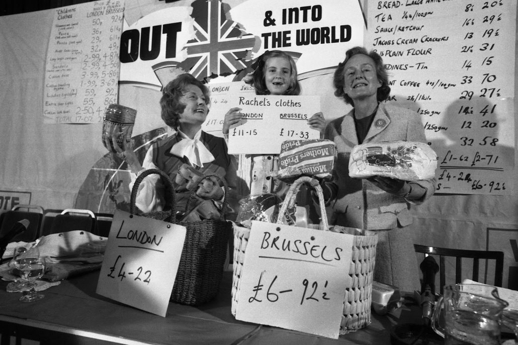 Social Services secretary, Mrs Barbara Castle, left, her seven year old great-niece Rachel Hilton and Mrs Joan Marten, wife of Neil Martin, Chairman of the anti-Common Marketeers (unseen) display goods they brought in London and Brussels with their retrospective prices for comparison during a press conference at the Waldorf Hotel in London, England on May 29, 1975. Mrs. Castle is one of the Labour Party's anti-marketeers. (AP Photo/Peter Kemp)