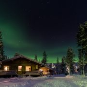 Aurea borealis over cottages in Lapland, Finland