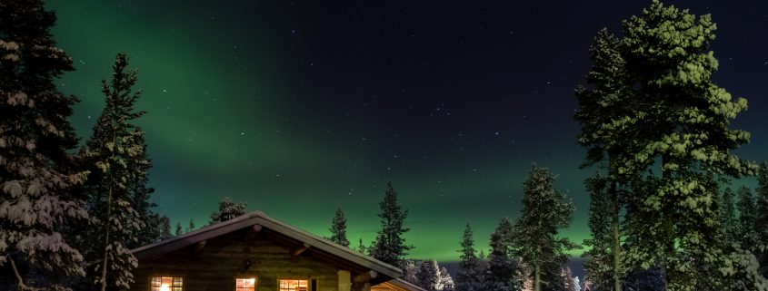Aurea borealis over cottages in Lapland, Finland