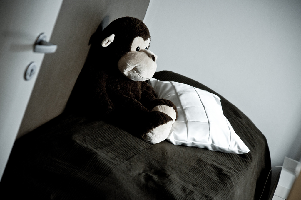 Smiling monkey plush toy sitting on bed, looking lonely.