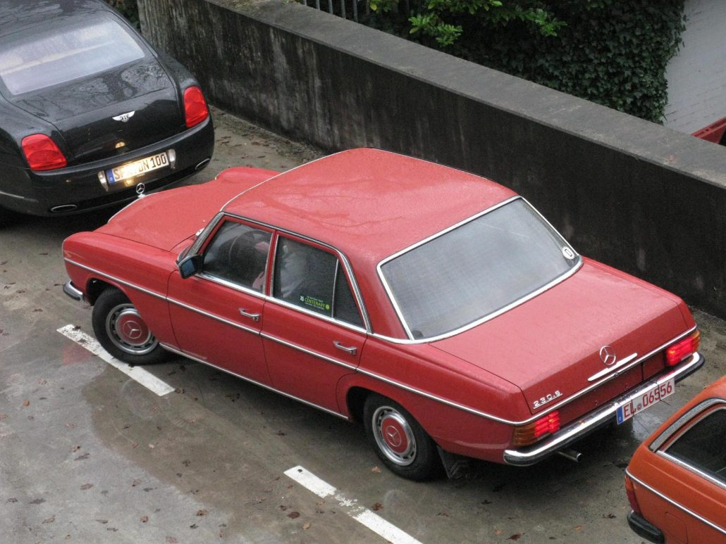 A red Mercedes Benz 230.6 sedan shot from above in an urban setting.