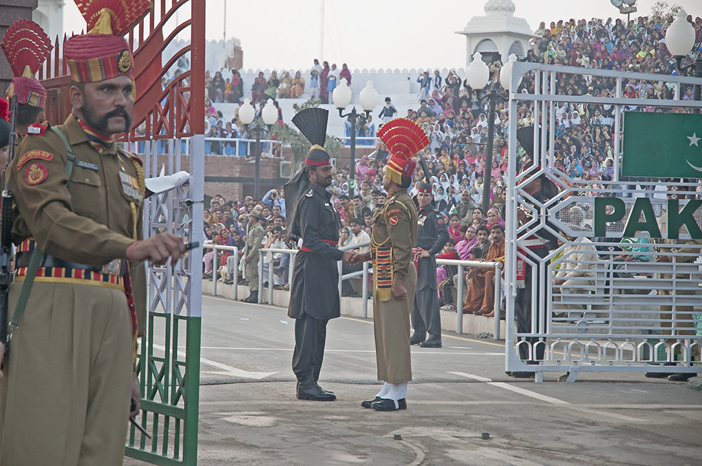"Old-school greeting between Pakistan and Indian border guards. The photographer describes this tradition: ""Thousands flock on both sides to watch the drill, which is performed with precision and showing some sort of mock belligerence which borders on the farcical! Spectators from both sides try to out-shout each other with patriotic slogans."" Photo credit: Koshy Koshy."
