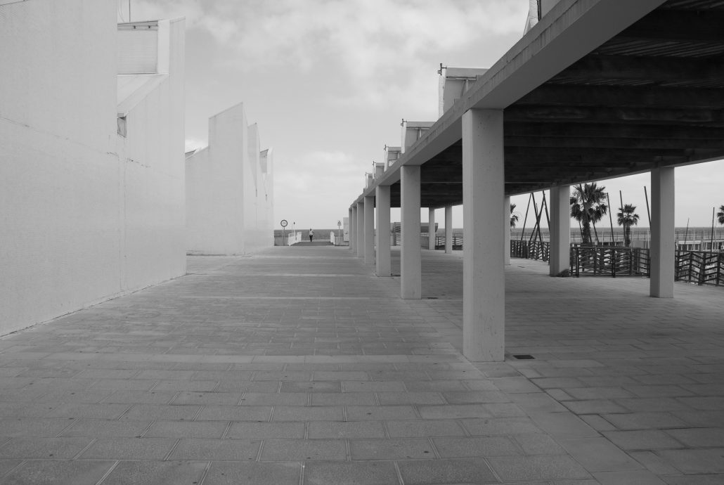 A person standing alone in the distance, at a pier maybe, surrounded by blank facades.