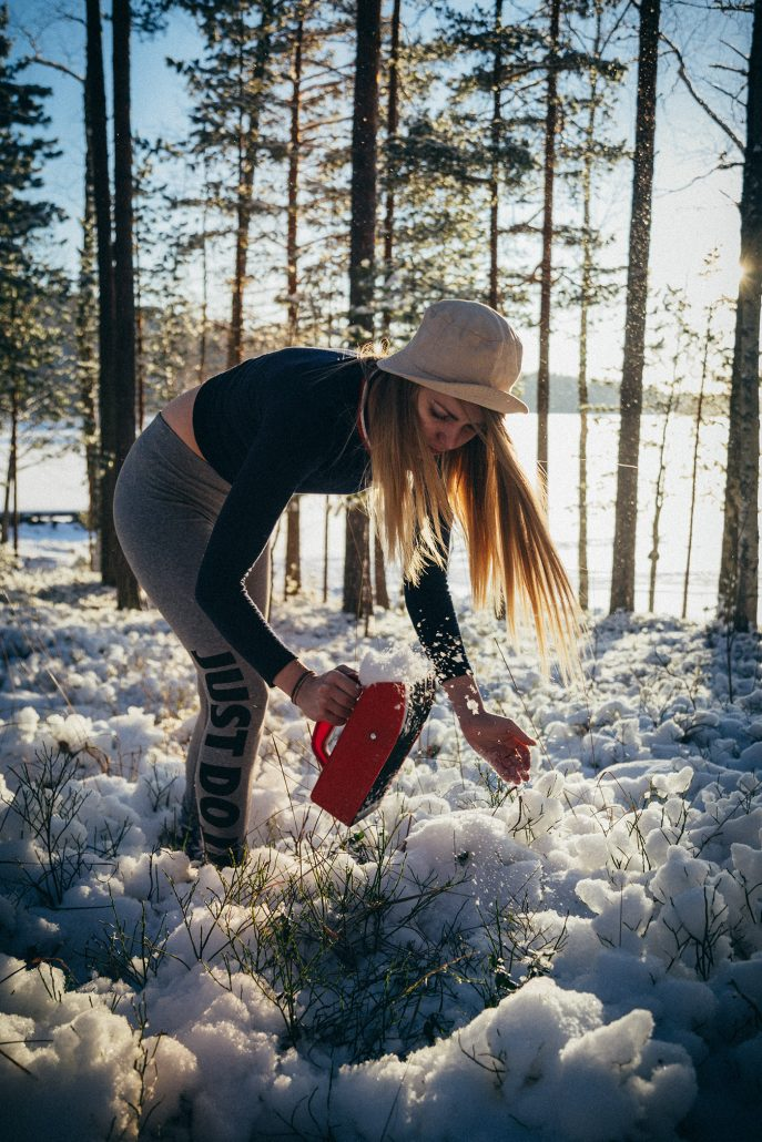 Girl trying to pick berries in snowy wintery shoreside forest, Asikkala, Finland.
