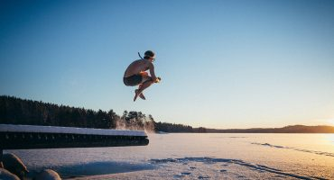 Young man jumping into icy lake, like it was summer. Photo in Asikkala, Finland.