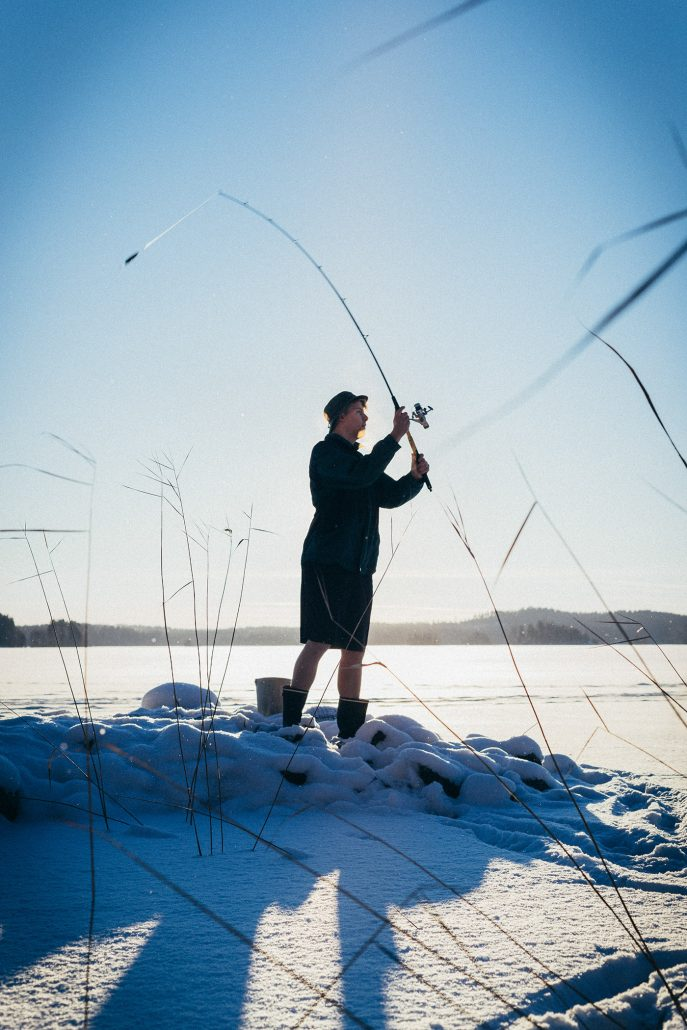 Young man by icy lake, trying to fish. Photo from Asikkala, Finland.