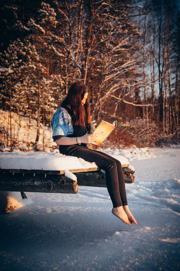 Young woman reading by an icy lake in wintery Asikkala, Finland.