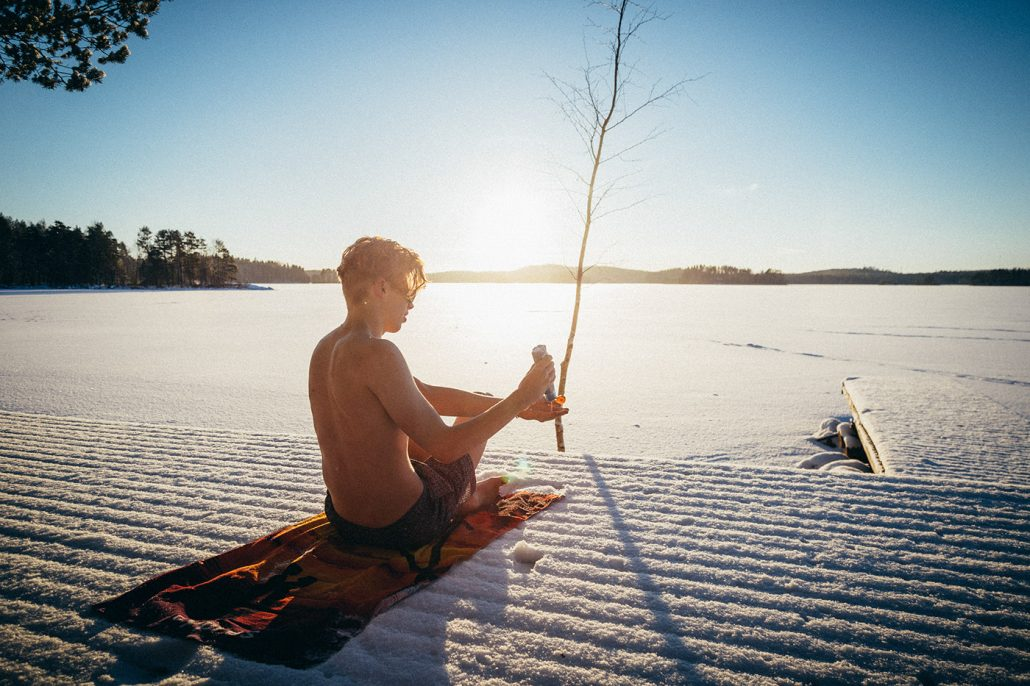 Young man putting on sun tan lotion by icy an icy lake in wintery Asikkala, Finland.