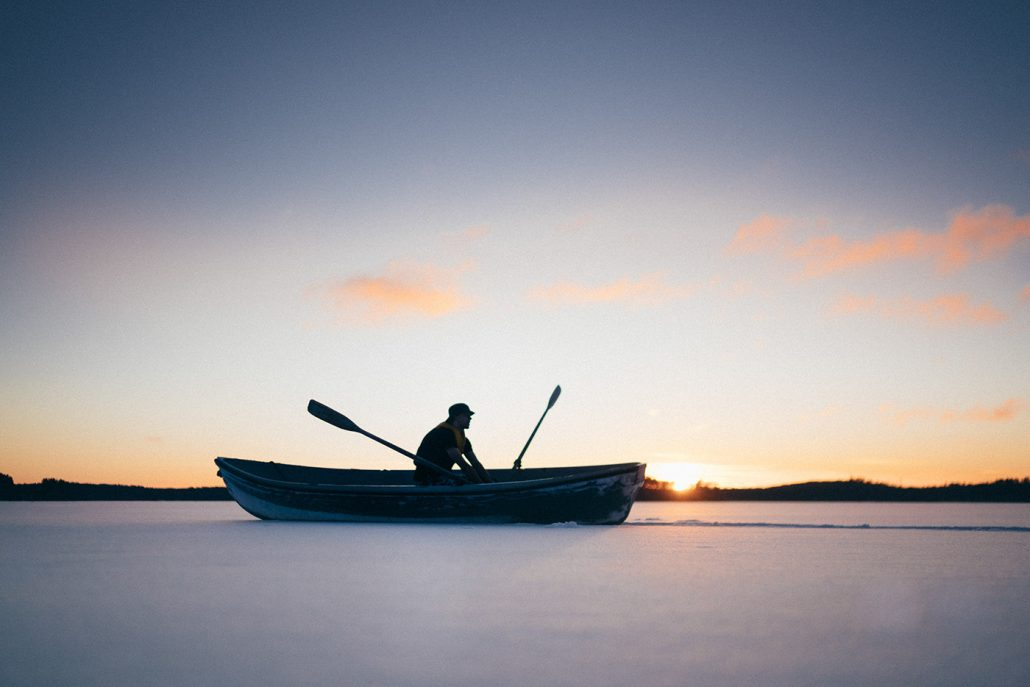 Young man stuck with rowboat in snow on icy lake, Asikkala, Finland.