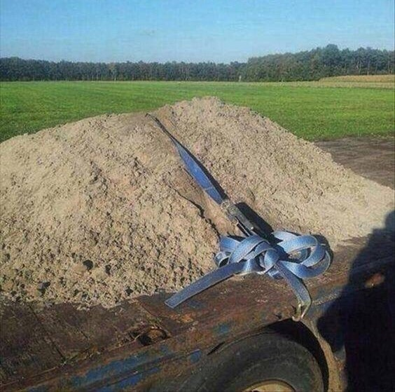 Load of dirt secured with belt