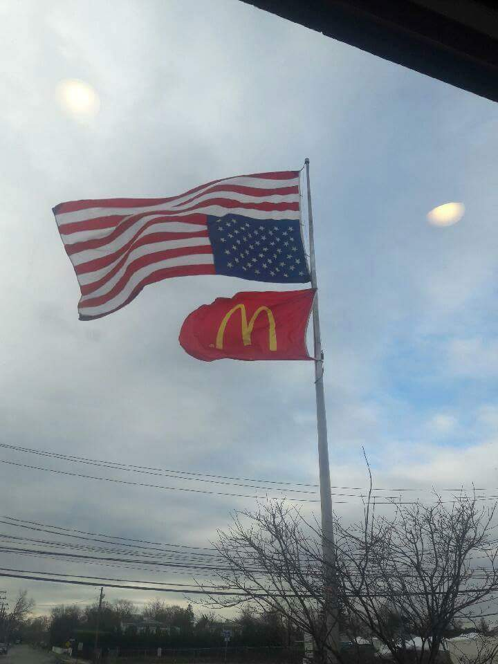 Upside down USA flag above McDonalds flag on suburban flagpole
