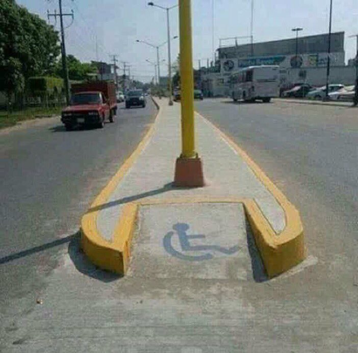 Wheel chair ramp in the middle of road with impossible, blocking light pole