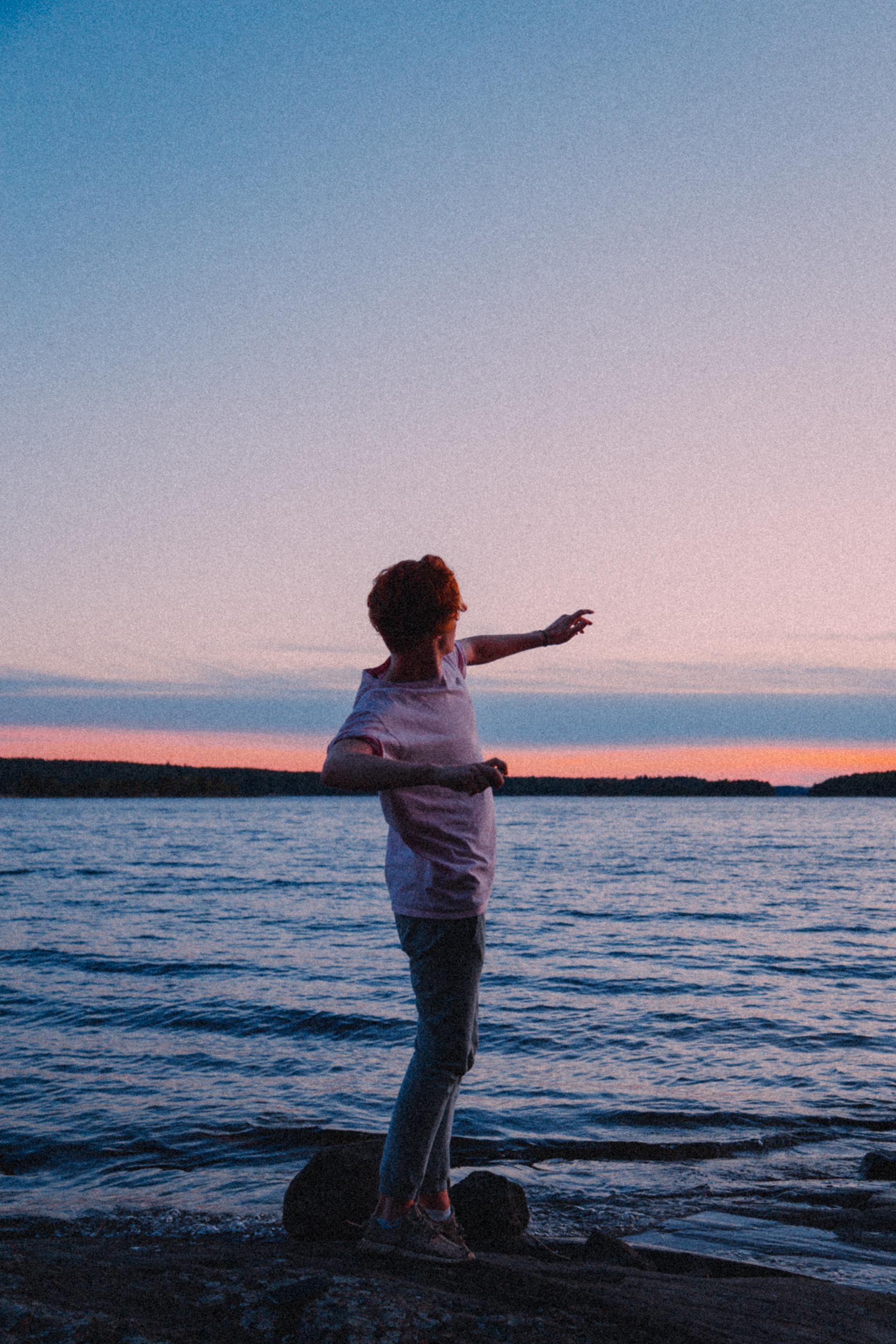 Young man throwing a stone into a lake, during sunset.