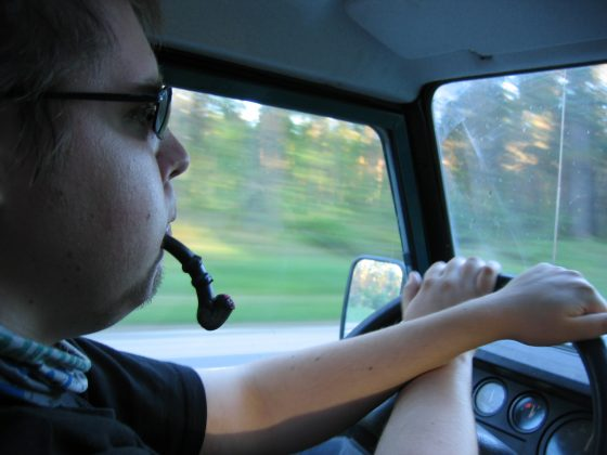 Man eating liquorice pipe candy while driving
