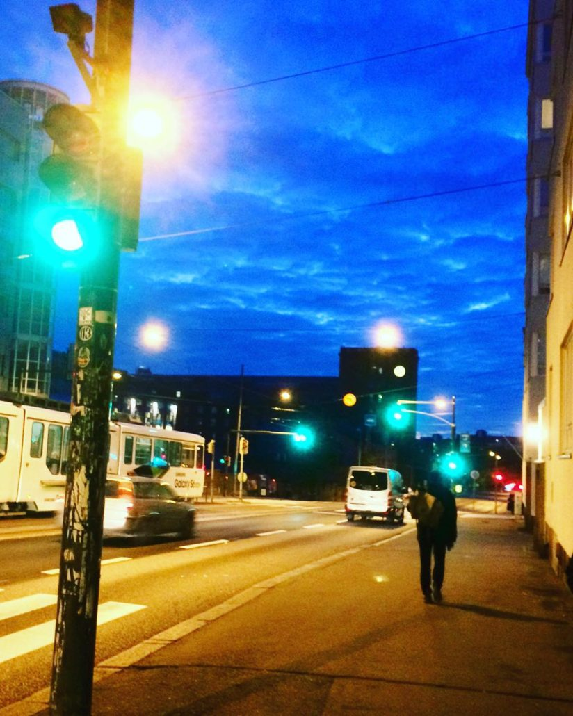 Autumnal view of Hämeentie in Kallio, Helsinki (Sörnäinen). The sky is intensely blue, just after sunset, which contrasts to bright street and traffic lights. A tram is also passing by.