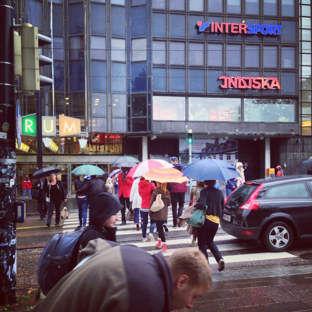 Rainy August afternoon  on Simonkatu, Helsinki. The forum shopping mall can be seen across the street, which is packed with pedestrians.
