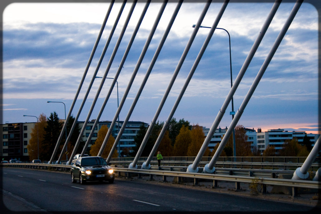 Beautiful autumn scene in Oulu, Finland suburb. Car driving over bridge surrounded by colorful foliage.