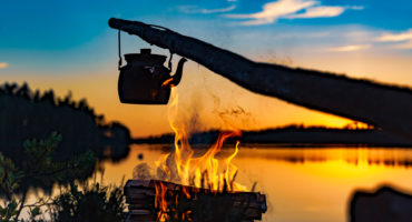 Coffee pan over campfire in lake countryside landscape, during a summer sunset